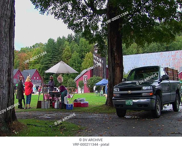Families picnic near trees and red barns at a Country Fair in Vermont