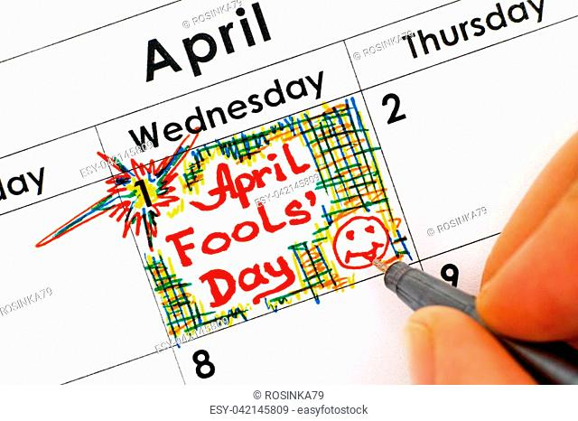 Woman fingers with pen writing reminder April Fools Day in calendar. Close-up