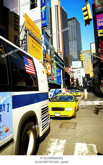Bus and yellow taxi moving on a road, Times Square, Manhattan, New York City, New York State, USA