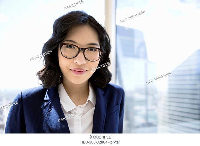Portrait smiling businesswoman at urban office window