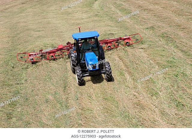 New Holland T4050 tractor with H5270 tedder in alfalfa from high angle view; New Holland, Pennsylvania, United States of America