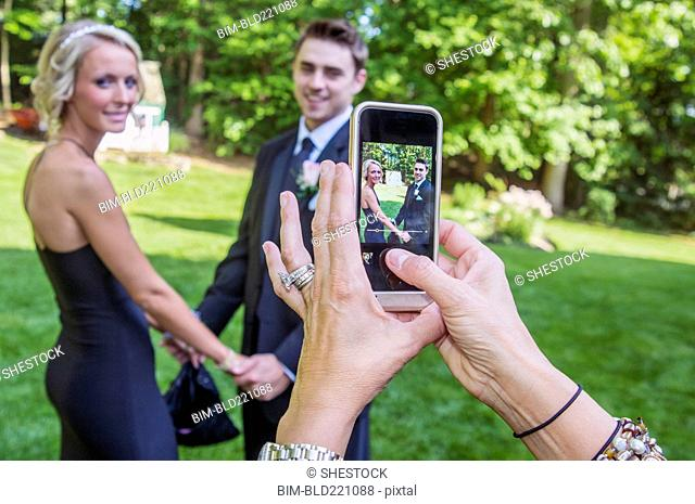Woman taking cell phone photograph of couple