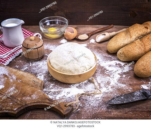 wheat yeast dough for bread and rolls in a wooden bowl on a table in the middle of the ingredients, top view