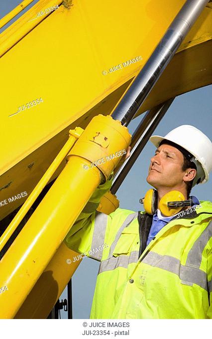 Construction worker examining hydraulic cylinders of bulldozer