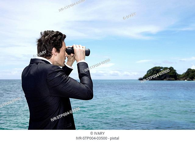 A businessman posing with binoculars on a dock