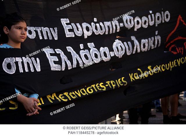 "Refugee child looks through banner. Writing """"Europe - Fortress Greece - Prison"""". 16.03.2019 | usage worldwide. - Athen/Greece"