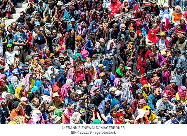 Large crowds of locals und tourists are watching monks with big wooden masks and colorful costumes performing ritual dances at Hemis Festival in the courtyard...