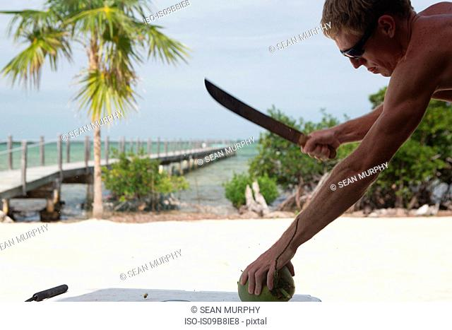 Man about to cut coconut with knife