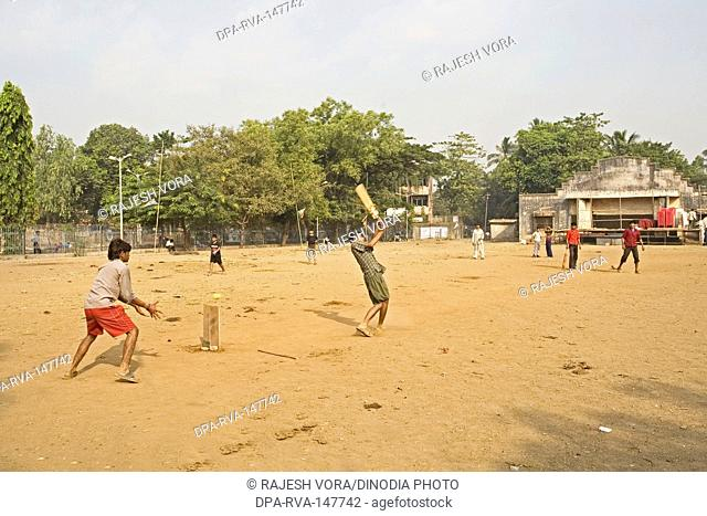 Children playing a game of cricket in an open community ground in a slum Khotwadi ; Santacruz ; Bombay now Mumbai ; Maharashtra ; India
