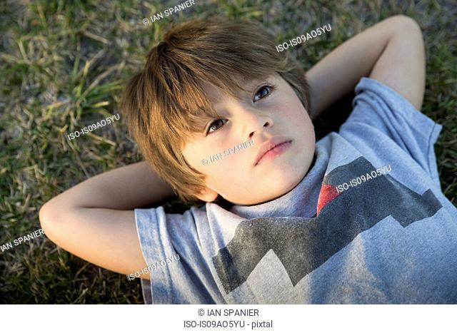 Portrait of boy lying on park grass gazing up