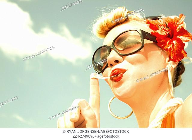 Low perspective of smiling retro blonde pinup woman with red lips, sunglasses and flower in hair chewing gum against of blue sky. Fashioning cool