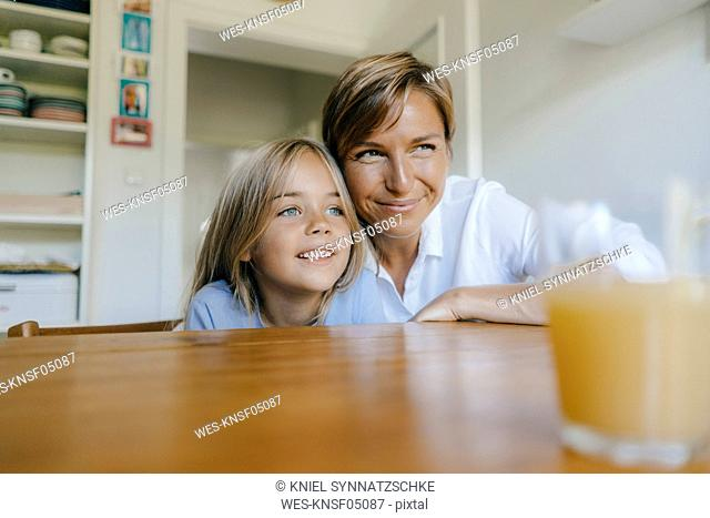 Smiling mother and daughter sitting at kitchen table at home
