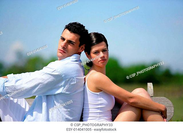 Young couple sat back to back on bench