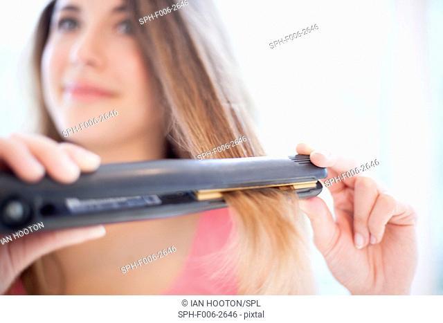 MODEL RELEASED. Woman using hair straighteners