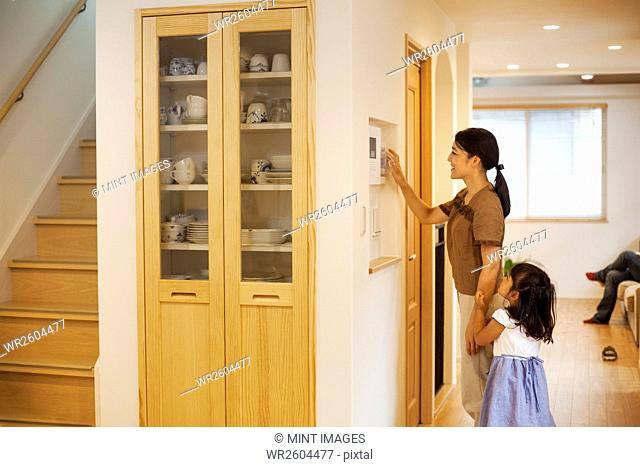 Family home. A woman adjusting the thermostat on a wall in the house