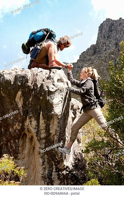 Hiking couple climbing rock formation