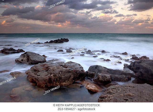 Rocky beach shoreline during sunset at Key West, Florida, USA
