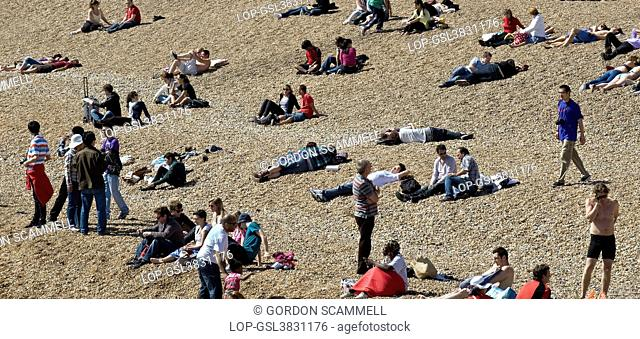 England, City of Brighton and Hove, Brighton. People relaxing on the pebble beach at Brighton
