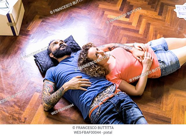 Daydreaming couple lying on the floor of new home