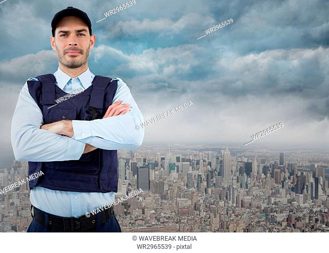 Security guard with arms folded against skyline and clouds