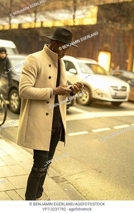 stylish man using phone at street, Munich, Germany