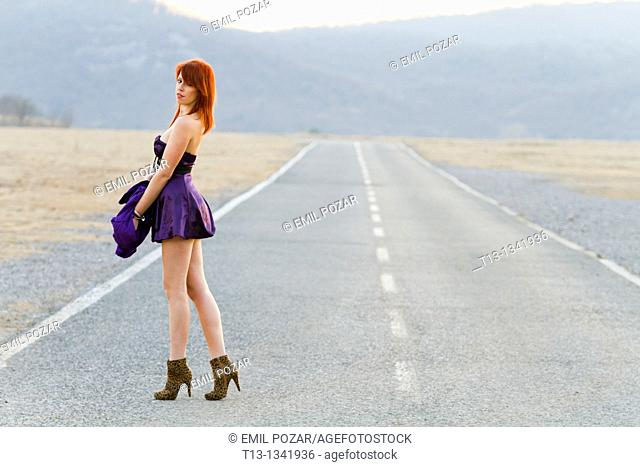 Walking on the road in a very seductive clothing young woman