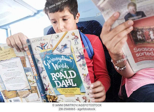 10 years old Caucasian boy reads Roald Dahl Book on public transport,UK