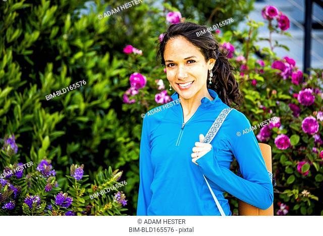 Hispanic woman carrying yoga mat in garden