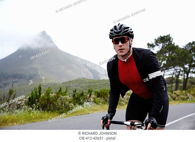 Portrait confident, determined male cyclist cycling on road