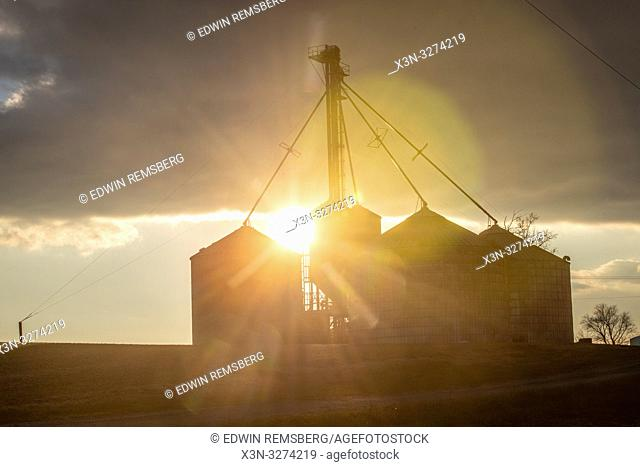The setting sun peaks out behind grain silos, Laytonsville Maryland