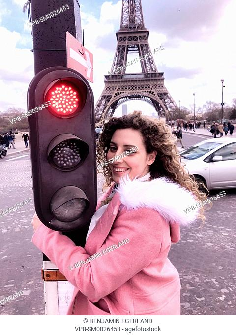 young happy Millennial tourist woman at street embracing red traffic lights, next to touristic sight Eiffel Tower, in Paris, France