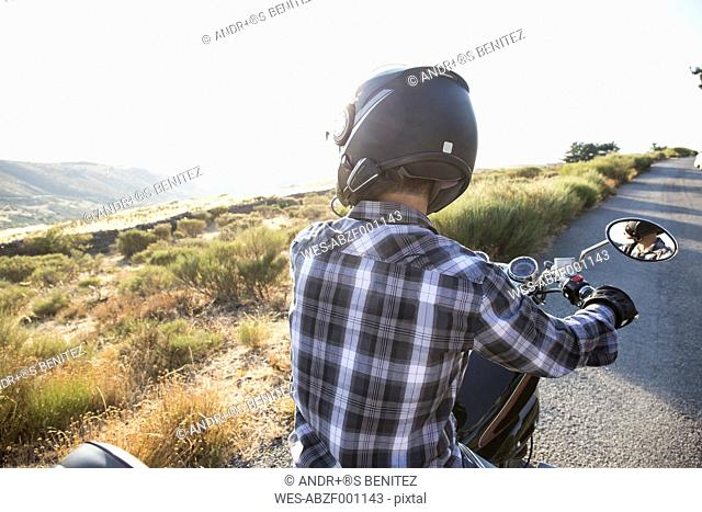 Back view of man on motorbike looking at view