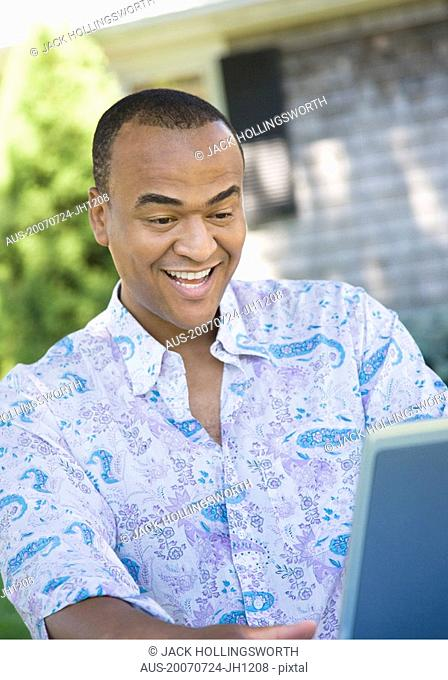 Mid adult man looking at a laptop and laughing