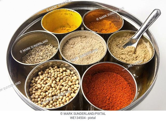 Stainless Steel Masala Dabba with a Selection of Indian Spices and a Measuring Spoon