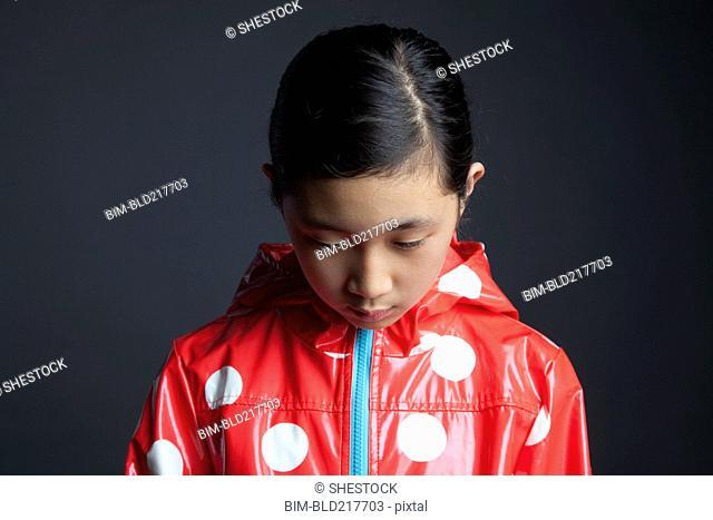 Sad Asian girl wearing raincoat