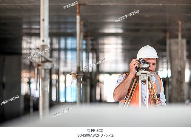 Mid adult male surveyor using theodolite on construction site