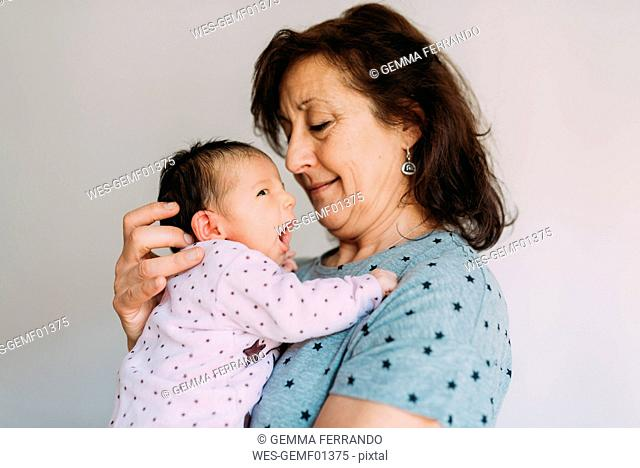 Grandmother holding her yawning granddaughter
