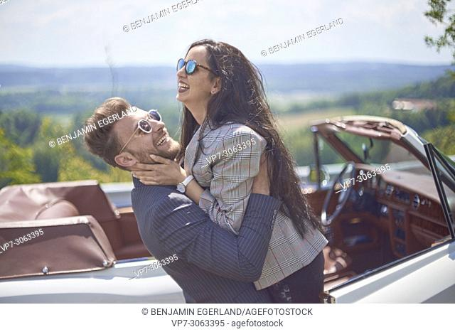 Vibrant couple falling in arms in front of luxury oldtimer car. Turkish ethnicity. Blogger Adem Bayalan. Bavaria, Germany
