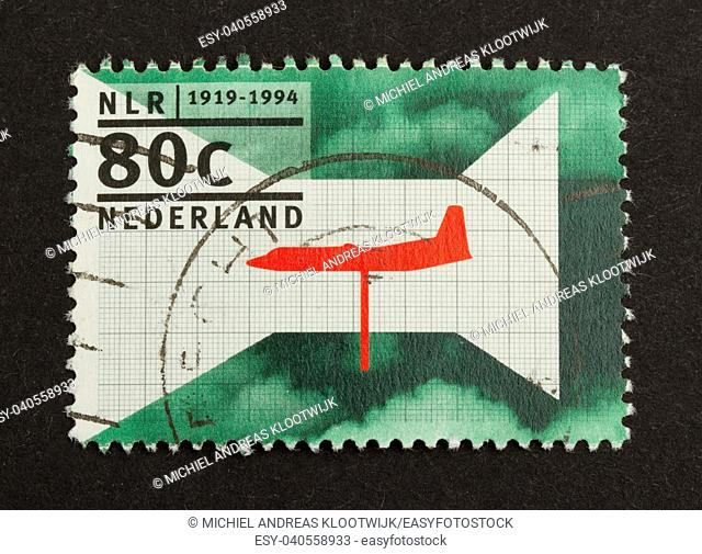 HOLLAND - CIRCA 1990: Stamp printed in the Netherlands shows a red airplane, circa 1990