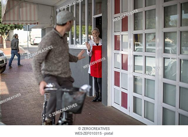 Shop assistant waving at man on bicycle outside shop