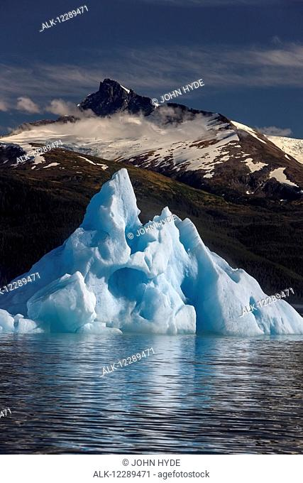 An iceberg floats on the calm waters of Holkham Bay, Tracy Arm-Fords Terror Wilderness, Tongass Forest, Alaska. Mt. Sumdum and Sumdum Glacier in the distance