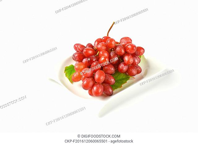 bunch of washed red grapes on white plate