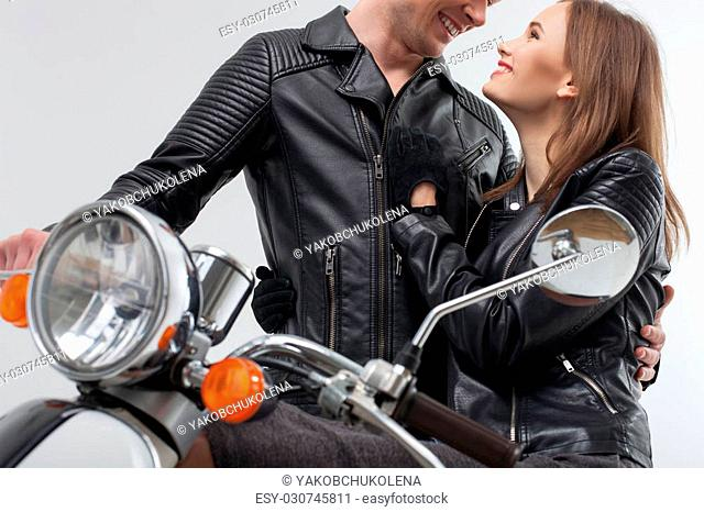 Attractive two bikers are made a romantic stop during their journey. The man is standing near the scooter and embracing the woman