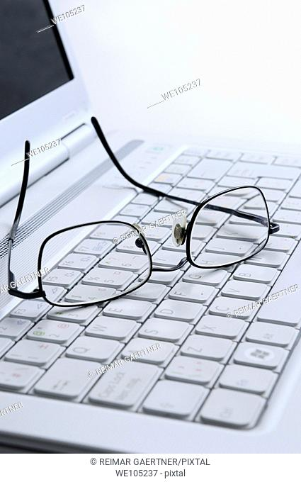 Reading glasses resting on the white keyboard of an open laptop computer