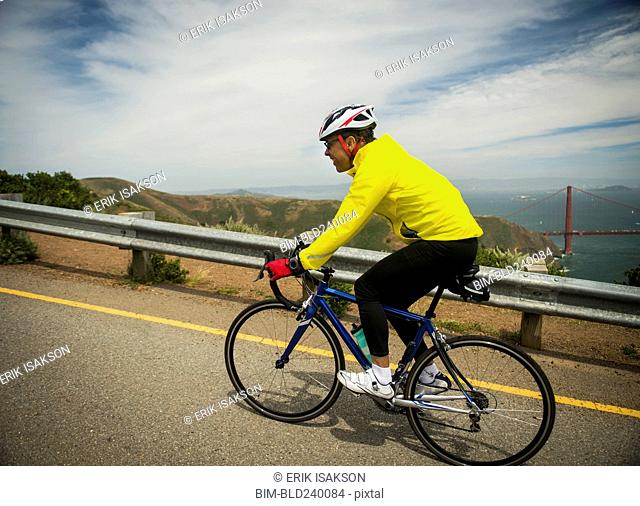 Hispanic man riding bicycle on waterfront road