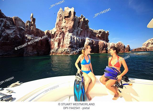 two tourists sitting on the edge of a boat with snorkeling gear at los islotes national marine park espiritu santo island, la paz baja california mexico