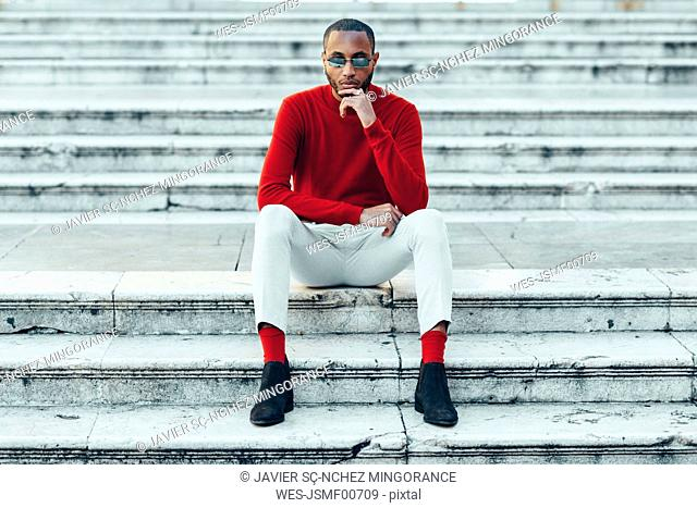 Portrait of stylish young man wearing red pullover and socks sitting on stairs