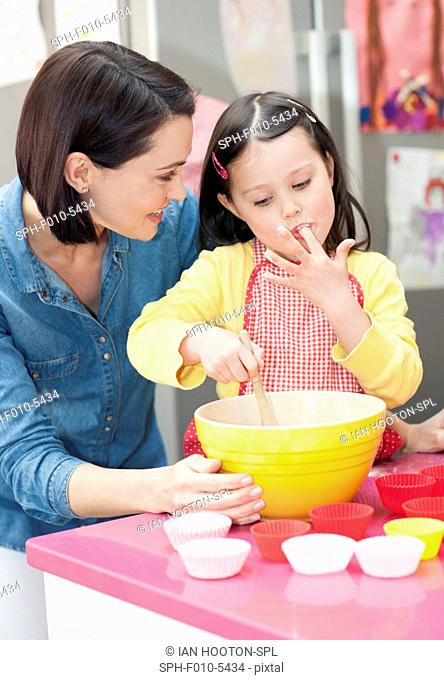 MODEL RELEASED. Mother and daughter baking