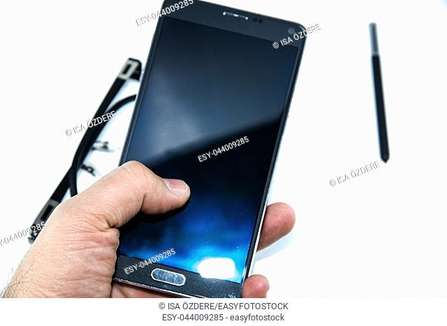 man finger touch on big smart phone with smart pen pen in hands isolated on the white background and with eye glasses