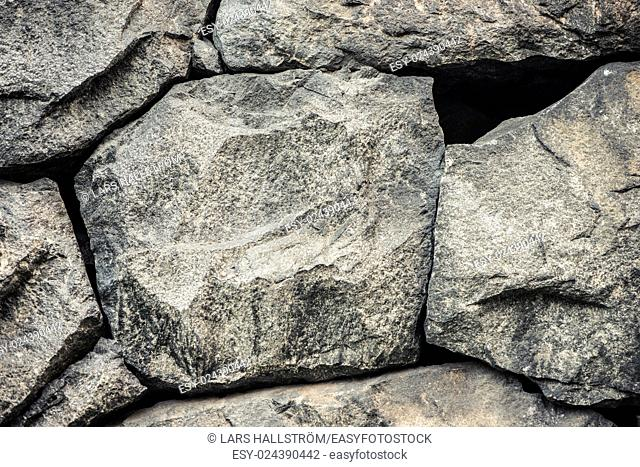 Stone background, rock wall backdrop with rough texture. Abstract, grungy and textured surface of stone material. Nature detail of rocks